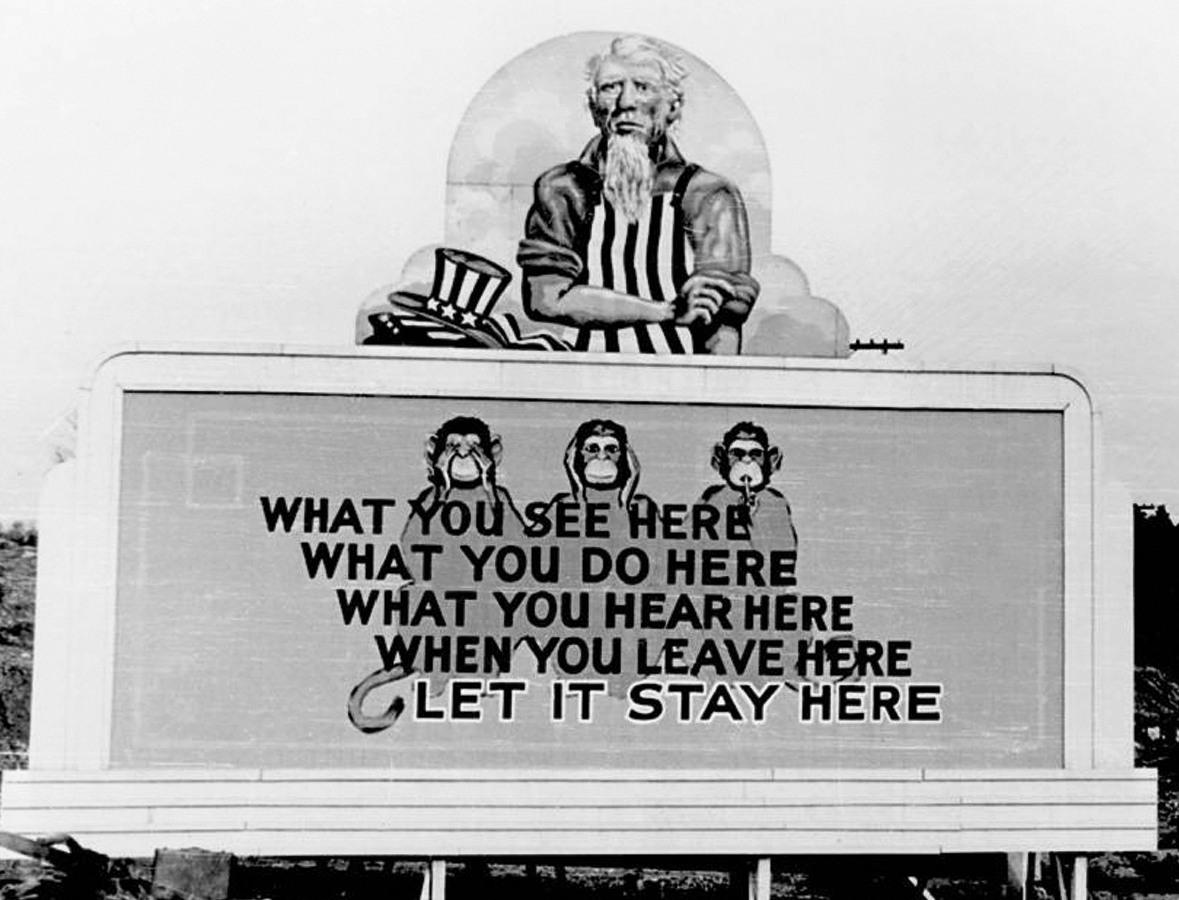 The billboard shows three monkeys and text reading: What you see here, what you do here, what you hear here, when you leave here, let it stay here. On top of the billboard is an old man with gray hair, long gray beard and black-and-white vertically striped shirt and a hat by him side with the same pattern.